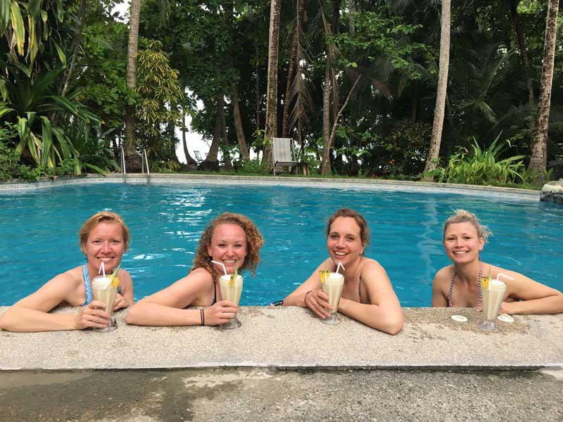 Four women drinking cocktails in the pool