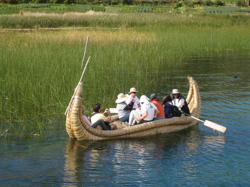 people in traditional boat on lake titicaca Peru