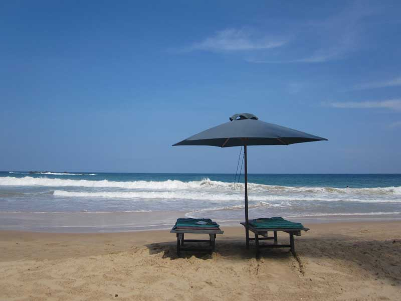 sandy beach with two sunloungers and parasol