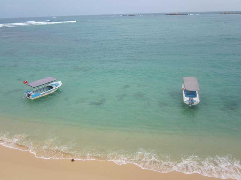 Aerial shot of blue sea and sandy beach with boats