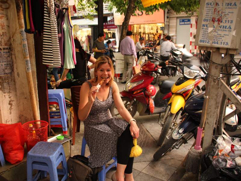 Woman sitting on a stool in the street eating food