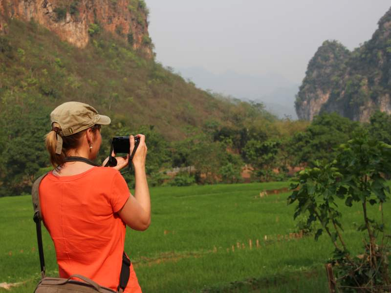 Woemn taking picture o the green scenery
