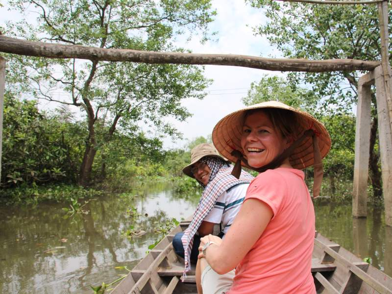 Woman smiling with Vietnamese hat on sitting in boat
