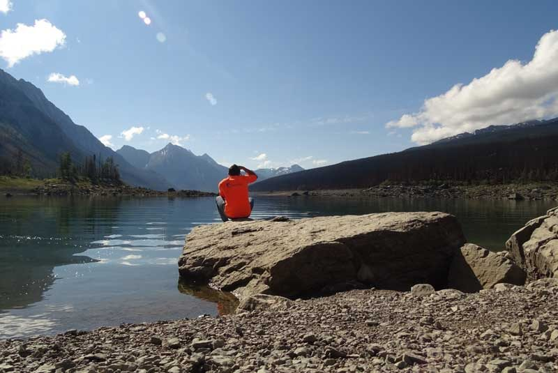 Person sitting on rock looking at view of lake and mountain