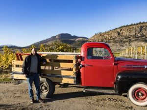 Man standing in front of an old fashioned red pick up truck