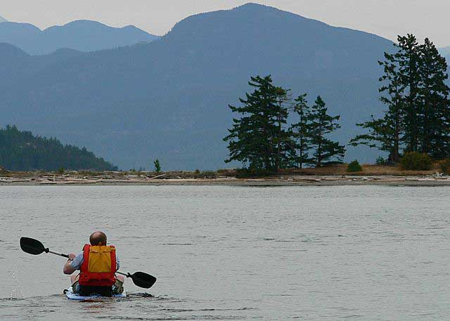 Solo person kayaking with mountains in background