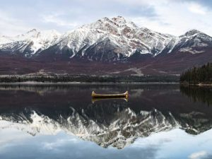 Snowy mountain with lake and empty kayak