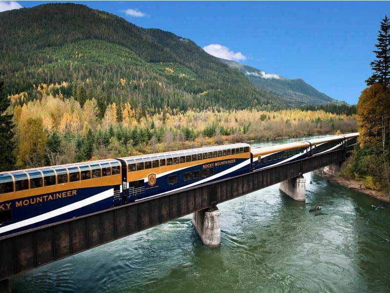 Train on bridge over water with mountains
