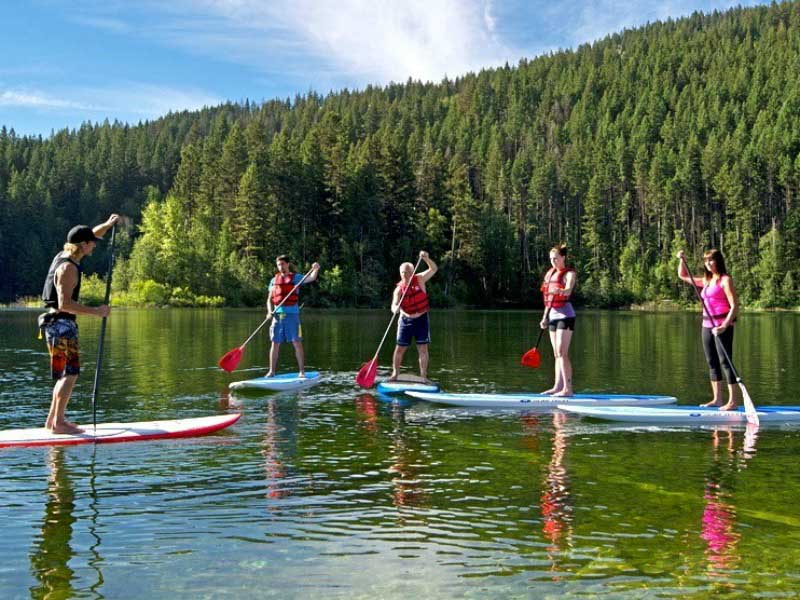 3 people standing on paddle boards in lake