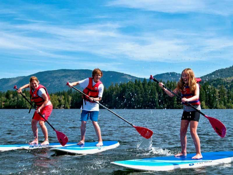 3 people standing on paddle boards having fun