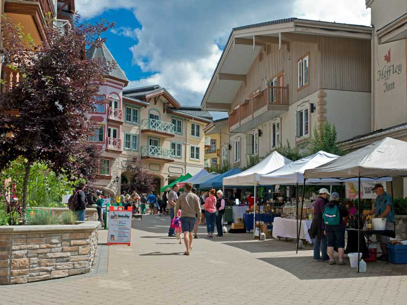 Market stalls in town with buildings and people walking