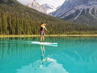 Person on stand up paddle board in blue lake with mountains