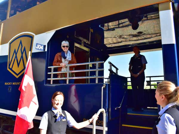 Woman standing on train with Canadian flag