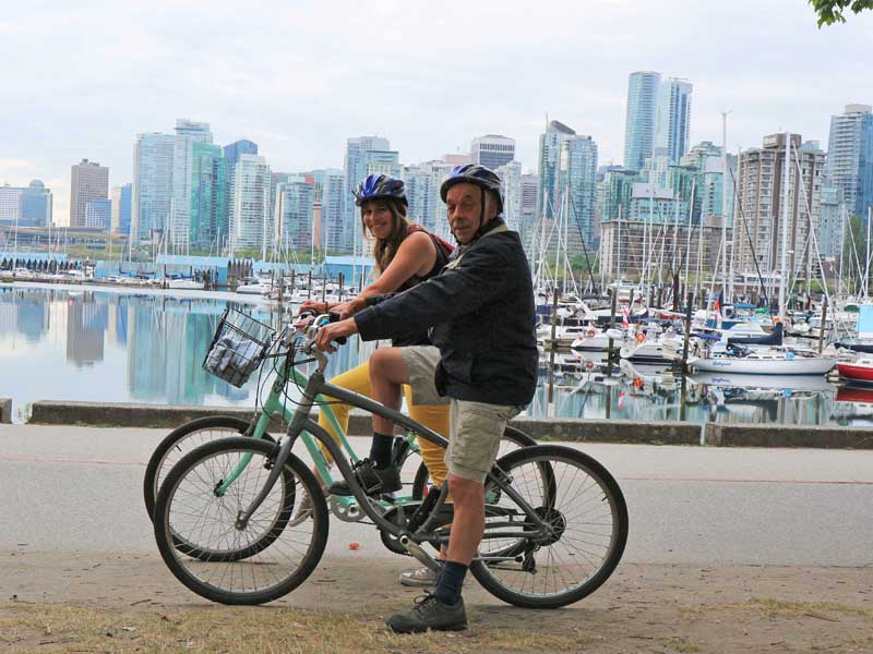 Two people on bikes with Vancouver city skyline