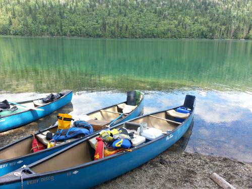 Canoes in a row on shore and lake