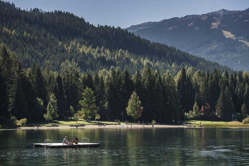 People sitting on pontoon in lake with trees