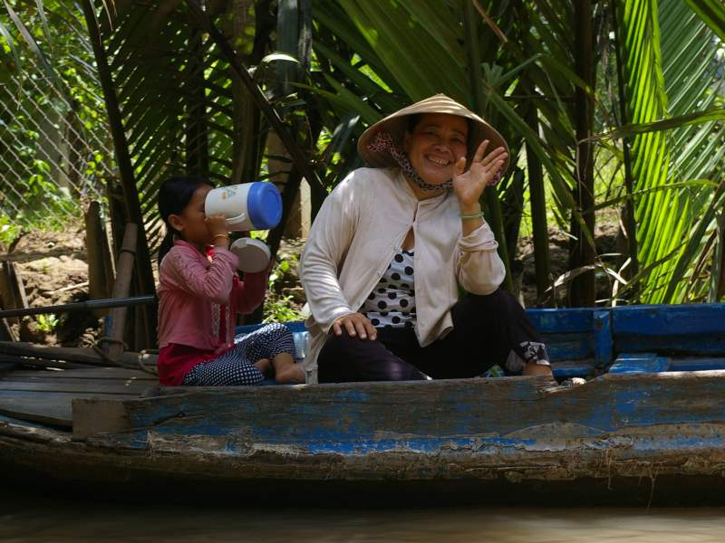 Lady on boat with child smiling and waving