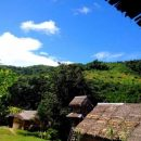 Green hills, blue sky and longhouse cabin