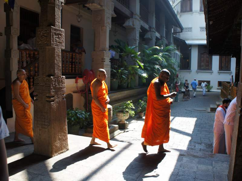 Three monks walking across to temple