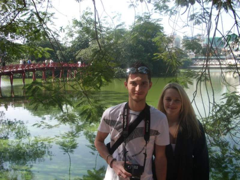 Couple standing infront of red bridge