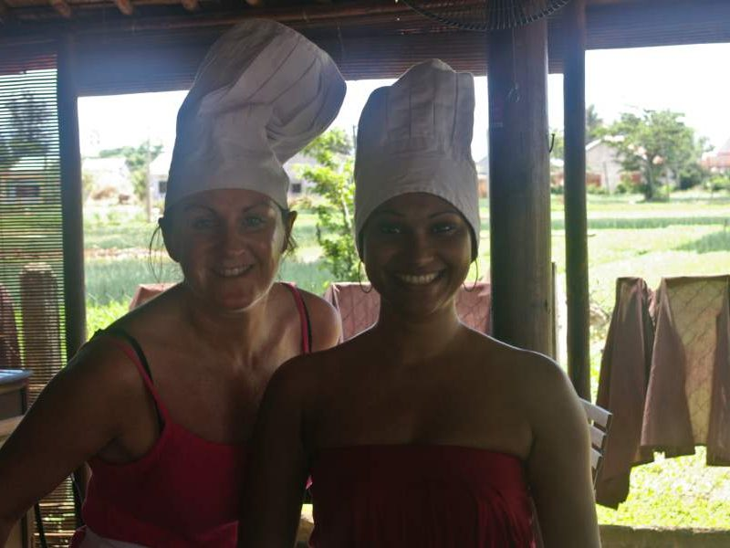 Two women smiling at camera with Chefs hat on
