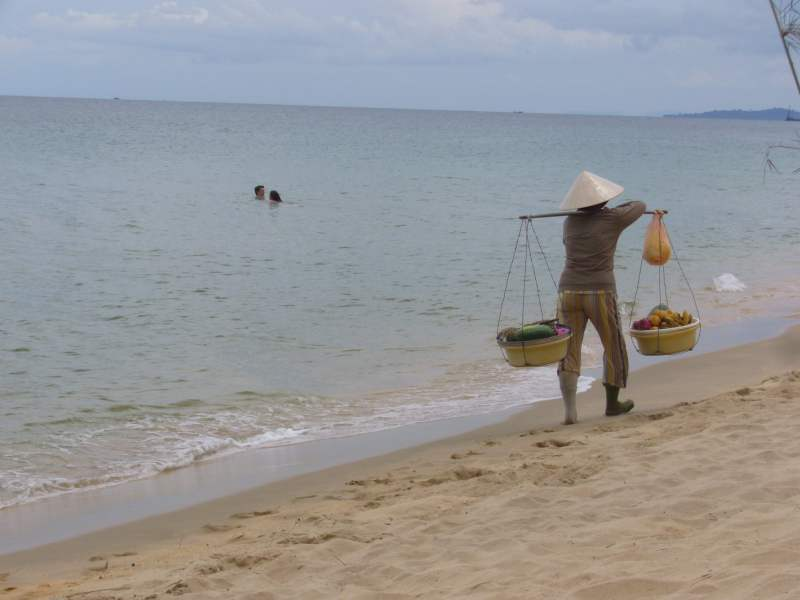 Local man carrying fruit to sell on beach
