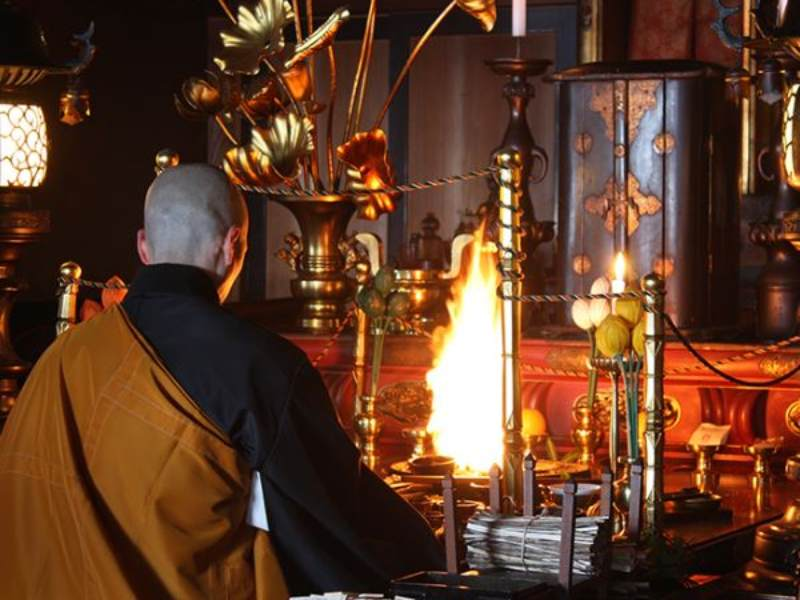 Monk praying in front of fire temple