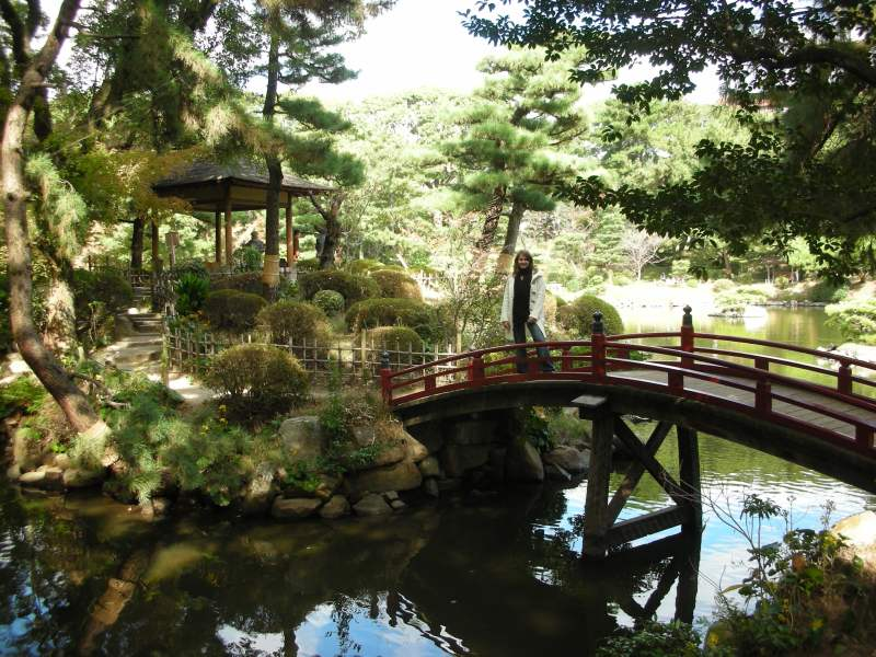 Bridge over pond and garden with woman standing in the middle