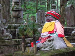 small statue of baby with wolly hat and clothes on