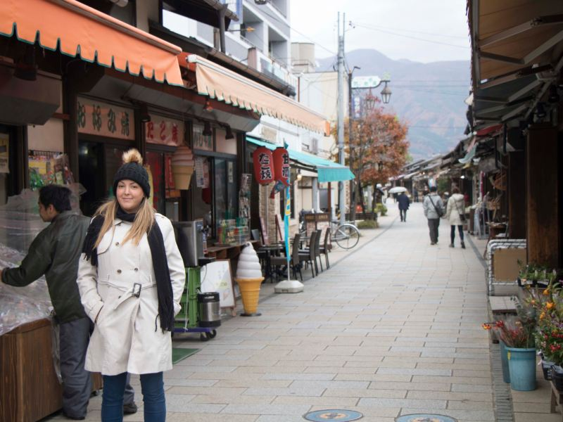 Woman standing in street surrounded by Japanese shops