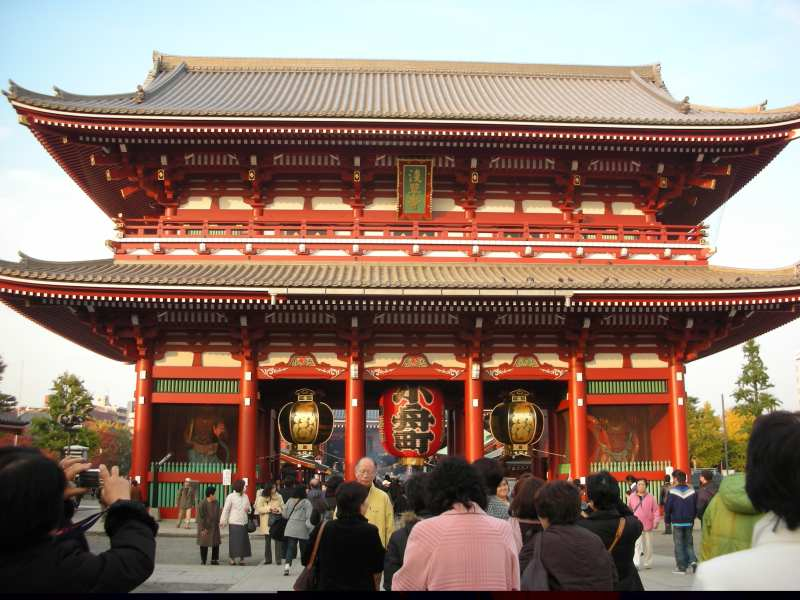 Large red temple with locals standing outsite