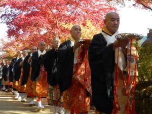 Line of monks holding plate walkling