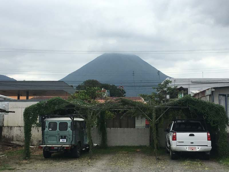 Volcano hidden in the clouds with two cars parked