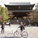 Woman cycling bike outside temple