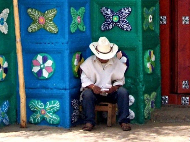 Man with cowboy hat in front of colourful walls