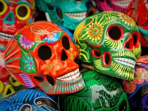 Decorated colorful skulls, ceramics death symbol at market, day of dead