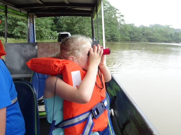 Girl using binoculars looking out over river