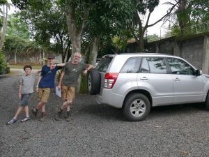 Family leaning on eachother against car