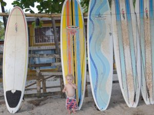 Young boy standing with surfboards