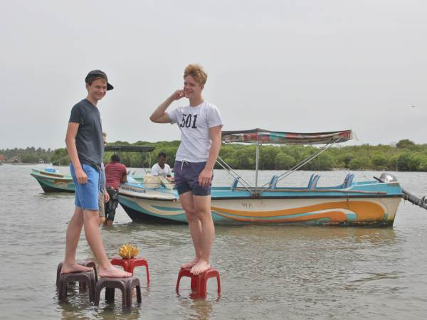 Boys standing on chairs in the ocean