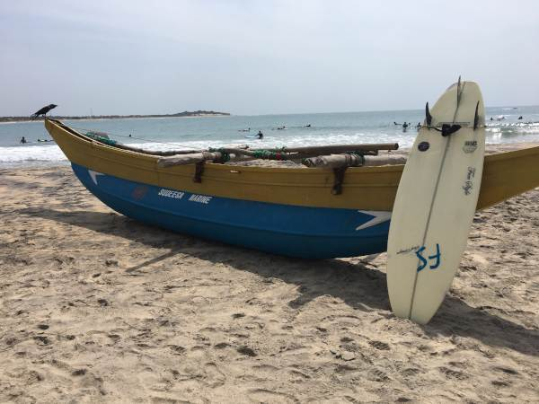 Surg Board against Boat on Sandy Beach