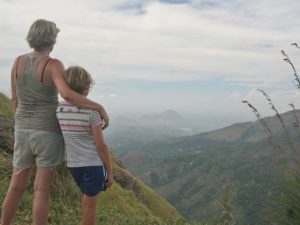Mother and son looking out of green valley