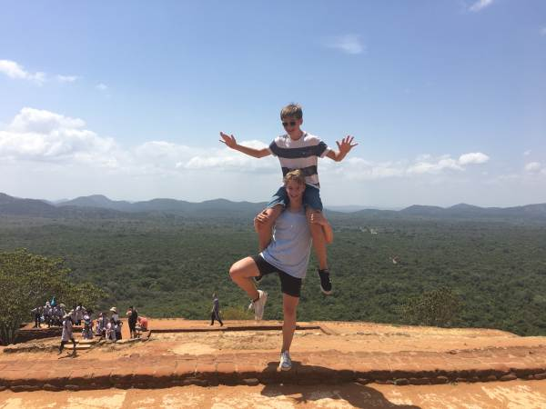 Boy on top of brothers shoulder at top of rock