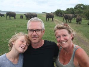 Family smiling with elephants in background