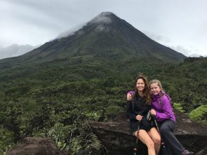 Woman and child sitting at base of volcano