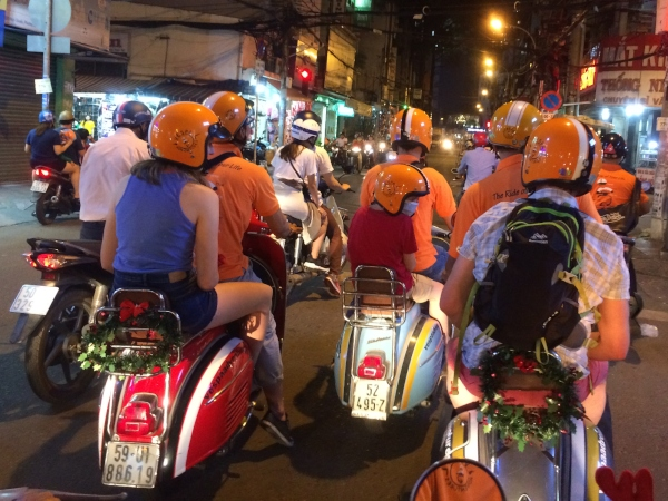 family riding pillion on vintage vespas in ho chi minh city