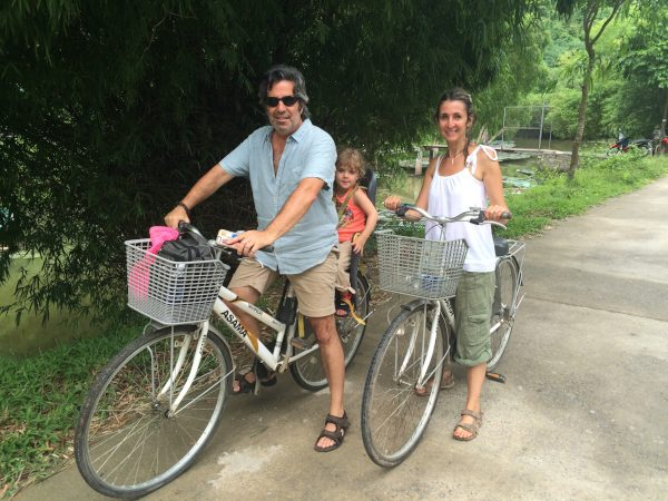 Family cycling through green
