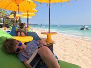 Two young boys relaxing at beach with book