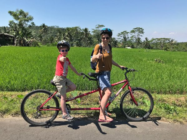 Mother and son cycling through rice fields