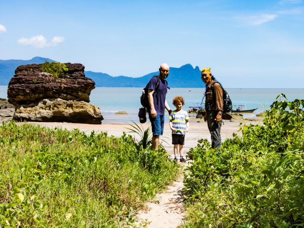 Local guide on beach with father and son